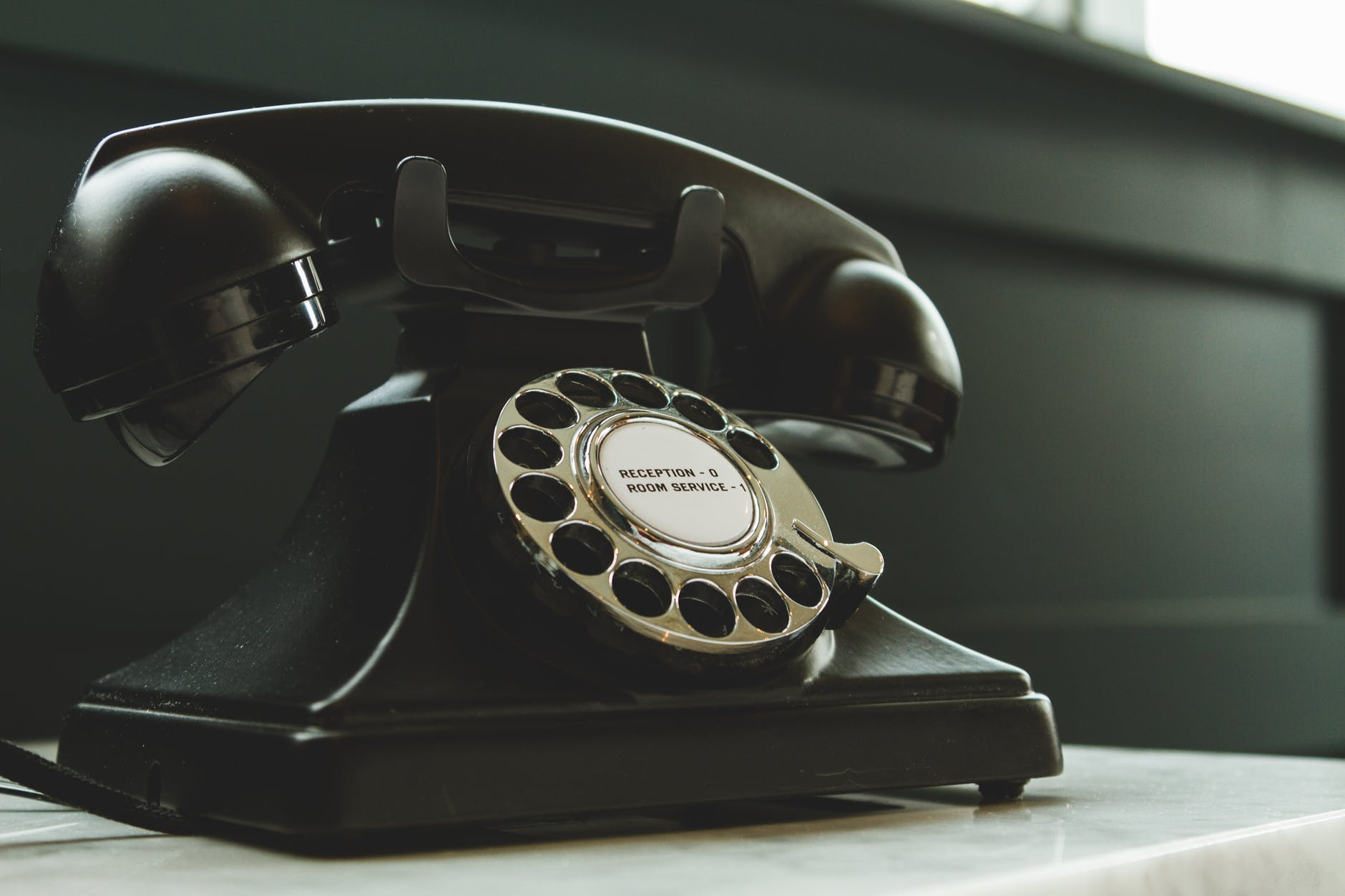 black rotary telephone on white surface - Contact