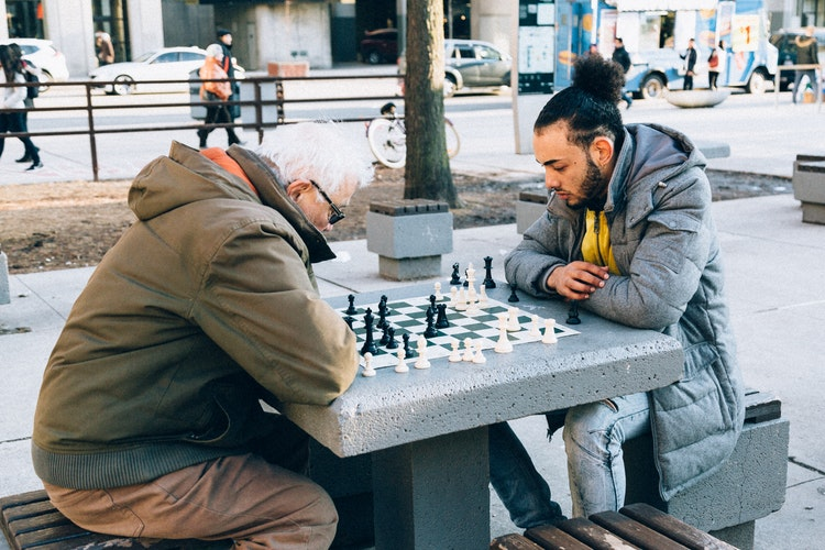 two man playing chess on table - 8 Reasons Why You Should Start Playing Board Games